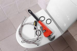 Plumber's tools on toilet | mid cities plumber