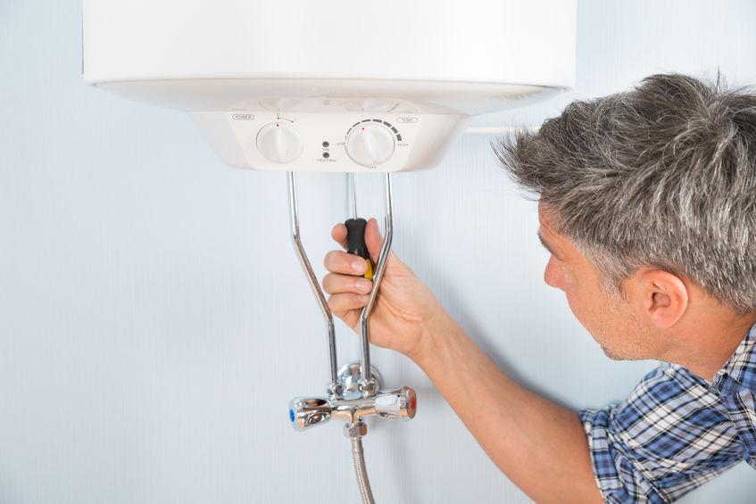 man repairing water heater in carrollton tx