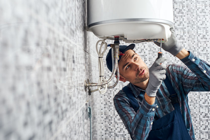 technician performing water heater replacement near me carrollton tx